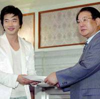 South Korean actor Kwon Sang Woo delivers a donation to Fukuoka Gov. Wataru Aso on Tuesday for victims of an earthquake that shook northern Kyushu in March 2005. | KYODO PHOTO