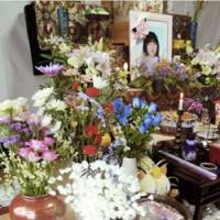 Flowers are offered in front of a photograph of Ayaka Hatakeyama at the family altar in Suzuka Hatakeyama's home on May 19. | KYODO PHOTO