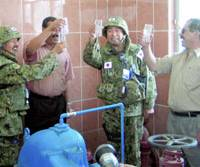 A toast is raised by Ground Self-Defense Force troops with local workers near the Iraq city of Samawah last month as they tried of water at a purification plant. | KYODO PHOTO
