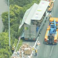 Workers gather scattered bottled detergent Thursday morning after a truck hit a guardrail and spilled its load on the Tomei Expressway in Nakai, Kanagawa Prefecture. | KYODO PHOTO