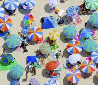 Colorful umbrellas provide some shade Sunday for people at Shirarahama beach in this southern resort town as the Meteorological Agency says the rainy season is likely over in most parts of the country.   KYODO PHOTO