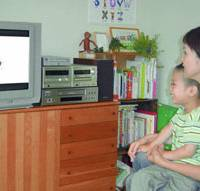 A mother and her child watch the Chilbie DVD picture book series on the TV in their Tokyo home last month. | KYODO PHOTO