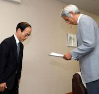 Toyota Motor Corp. Vice President Masatami Takimoto bows Thursday after handing over a report on its system for checking vehicle defects to a transport ministry official. | AP PHOTO