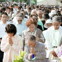 People offer prayers at Peace Memorial Park during the ceremony Sunday marking the 61st anniversary of the atomic bombing of Hiroshima.   KYODO PHOTO