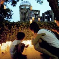 A mother and her child look at 'Peace Candles' placed around the Atomic Bomb Dome in Hiroshima on Sunday.   KYODO PHOTO