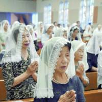 People attend morning Mass at Urakami Cathedral in Nagasaki on Wednesday to pray for victims of the 1945 atomic bombing. | KYODO PHOTOS