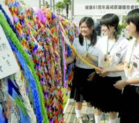 Junior high school girls hang paper cranes, which have become a symbol of peace and nuclear disarmament, Wednesday at Nagasaki's Peace Memorial Park.
