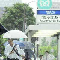 Commuters emerge from Kasumigaseki Station in Tokyo amid a downpour as Typhoon Maria approached the Kanto region Wednesday.   KYODO PHOTO