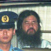 Shoko Asahara is driven from the Tokyo District Court to Metropolitan Police headquarters in July 1995.   AP PHOTOS
