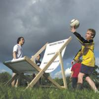 Kids play around a chair with a Yoko Ono-designed pattern at a royal park in London.   PHOTO COURTESY OF ANDY LANE/KYODO