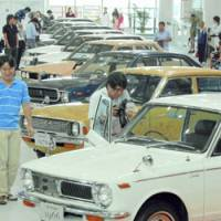 Visitors view past Toyota Corolla models Tuesday at an exhibition in Tokyo's Odaiba district. | KYODO PHOTO