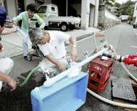 Officials from the Edajima Municipal Government in Hiroshima Prefecture provide water to a resident from a fire main.   KYODO PHOTO
