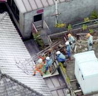 Men try to pull up a steel frame in Tokyo on July 23, 2005, after the capital was struck by its strongest quake in 13 years.   KYODO PHOTO