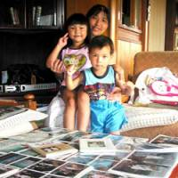 Harumi Kobayashi poses with her children in front of her vast collection of Imperial family photos.   AKEMI NAKAMURA PHOTO