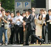 Former Livedoor Co. President Takafumi Horie walks past a phalanx of reporters as he arrives at the Tokyo District Court on Monday morning for his first trial session. | AP PHOTO