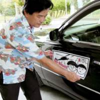 Ginowan mayor Yoichi Iha puts a sticker on an official vehicle Thursday to promote the resolution of issues related to the U.S. military base in the Okinawan city.   KYODO PHOTO