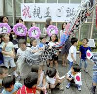 Children help put up a carp streamer to celebrate the birth of a boy to Princess Kiko on Sept. 6 in front of JR Mejiro Station in Tokyo.   KYODO PHOTO