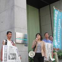 Michiko Yamaguchi, who got hepatitis C through a tainted blood product, uses a megaphone Sept. 4 to demonstrate at the Tokyo headquarters of Mitsubishi Pharma Corp., a defendant in a suit brought by her and 17 others. | TOMOKO OTAKE PHOTO