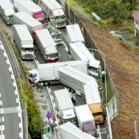 The Chuo Expressway in Nagano Prefecture is littered with crashed trucks and cars in a 21-vehicle pileup early Thursday.   KYODO PHOTO