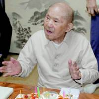 Tomoji Tanabe, the oldest man in Japan, celebrates his 111th birthday with a cake at his home Monday.   KYODO PHOTO
