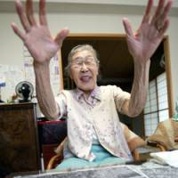 Toyo Ishii, 84, explains old aerial photos at her home in Tokyo. Ishii, a former military nurse, went public in June with the first eyewitness account of the burials of corpses and bones that could be linked to Unit 731, Japan's dreaded germ and biological warfare outfit. | AP PHOTO