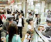 East Japan Railway Co. employees assist passengers at JR Tokyo Station after it temporarily suspended all operations on the Keiyo Line.   KYODO PHOTO