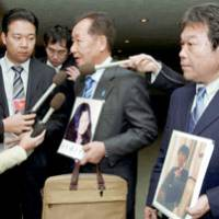 Shigeo Iizuka, whose younger sister, Yaeko Taguchi, was abducted to North Korea in 1978, fields questions from reporters as Teruaki Masumoto, chief secretariat of a group of relatives of abductees, stands by holding a photo of his own missing sister, Rumiko.   KYODO PHOTO