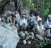 Members of Pacific War History Museum, a nonprofit group based in Ohshu, Iwate Prefecture, hold skulls found on New Guinea in June 2005. | PHOTO COURTESY OF PACIFIC WAR HISTORY MUSEUM