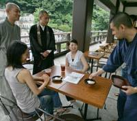 Monks chat with young female visitors while serving tea and sweets Aug. 9 at Kamiyacho Open Terrace, a cafe overlooking the cemetery in Komyoji Temple in Tokyo. | AP PHOTO
