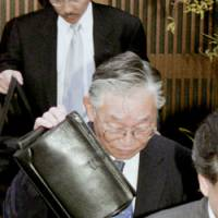 Police escort Takeshi Sato, a former executive of chemical maker Ishihara Sangyo Kaisha Ltd., from his home before his arrest Monday along with three others for illegal dumping of industrial waste.   KYODO PHOTO