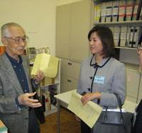 Tetsuro Takahashi, a former soldier held in China after World War II, shows officials from the Chinese Embassy in Tokyo around the Chukiren peace memorial museum in Kawagoe, Saitama Prefecture. The shelf holds copies of handwritten testimony by 45 Japanese convicted by China as war criminals. | KYODO PHOTO