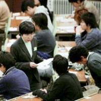 A supervisor hands out tests to applicants taking standardized college entrance exams in January at the University of Tokyo. More than 500 high schools across the nation have failed to provide an adequate curriculum for students to meet graduation requirements. | KYODO PHOTO