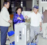 Voters cast ballots in Sunday's Okinawa gubernatorial election at a polling station in Naha. | KYODO PHOTO