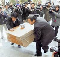 Police officers carry cardboard boxes Monday into the headquarters of Kinmirai Tsushin Inc. in Chuo Ward, Tokyo, as they search of evidence that the IP telephony company defrauded investors.   KYODO PHOTO