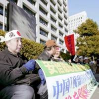 Plaintiffs gather Monday outside the Health, Welfare and Labor Ministry to demand that the government not appeal a court ruling that held it liable for failing to take adequate steps to resettle them from China after the war.   KYODO PHOTO