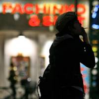 A man smokes as he waits at a pedestrian crossing near a pachinko parlor in central Tokyo last month. | AP PHOTO