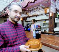 Eduardo Mira Bastista, a one-time counselor at the Portuguese Embassy in Tokyo, shows off a dish at his restaurant, Portugalia, which opened in Osaka in July. | KYODO PHOTO