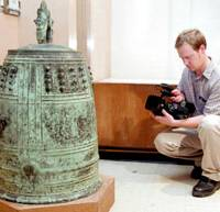 U.S. high school teacher Paul Creager films the Gokoku Temple bell, now housed in the Okinawa Prefectural Museum, in October.   KYODO PHOTO