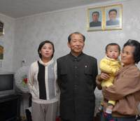 Kim Won Gyong and his family pose at their home in Pyongyang. On the wall are portraits of North Korea's founder, Kim Il Sung, and his son and heir, Kim Jong Il. | KYODO PHOTO