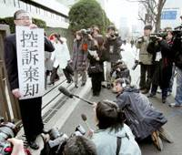 A supporter for defendants in the so-called Yokohama Incident shows a banner saying their appeal has been rejected Friday in front of the Tokyo High Court. | KYODO PHOTO