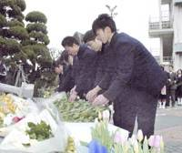 Students at Uwajima Fisheries High School in Ehime Prefecture place flowers in front of a cenotaph at the school's entrance Saturday. | KYODO PHOTO
