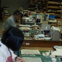 Licensed librarians mend historical documents at Chuo Library in Minato Ward, Tokyo, this month. Such behind the scenes work is also part of their job. | SETSUKO KAMIYA PHOTO