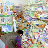 A supermarket clerk in Nanao, Ishikawa Prefecture, cleans up after a strong earthquake knocked products off the store's shelves in Hokuriku Sunday morning.