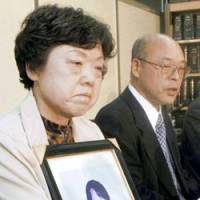 Katsuji and Haruyo Usui face reporters Wednesday after the Tokyo High Court ruled that their son, Takehito (in picture), committed suicide because he was bullied at school. | KYODO PHOTO