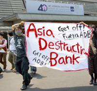 Demonstrators hold up a banner Friday in front of the main entrance of the Kyoto International Conference Center in Kyoto, where the Asian Development Bank was holding its annual meeting. | AP PHOTO