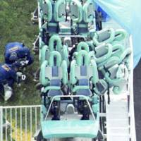 Police examine the Fujin Raijin II roller coaster at Expoland in Suita, Osaka Prefecture, after a rider was killed and 19 others were injured in an accident Saturday. The second car is the one tipped over resting on the guardrail. | KYODO PHOTO