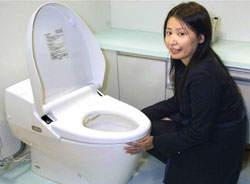 a toto co employee shows off one of the washlet at - Toto Bidet