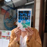 Radha Mainali, the wife of convicted murderer Govinda Mainali, covers her face with a booklet published by a support group for her husband, in Shibuya Ward, Tokyo, last month. | YOSHIAKI MIURA PHOTO