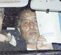 Hisato Obayashi is driven in a police vehicle to Aichi Police Station following his surrender Friday evening. ending a 29-hour standoff at his home in Nagakute, Aichi Prefecture.   KYODO PHOTO