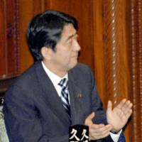 Prime Minister Shinzo Abe celebrates after the Lower House approves bills to reform the Social Insurance Agency in the early hours of June 1. | KYODO PHOTO
